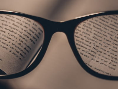 A pair of spectacles magnifying some text